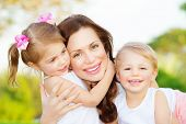 Picture of young mother hugging two little children, closeup portrait of happy family, cute brunette female with daughter and son outdoor in spring time, smiling faces, happiness and love concept