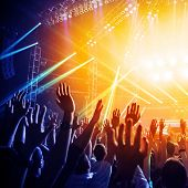 Photo of many people enjoying rock concert, crowd with raised up hands dancing in nightclub, audienc