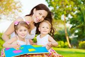Image of cute young female with two little children read book outdoors, cheerful mother and two pret