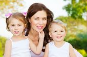 Photo of beautiful woman with two cute kids, closeup portrait of young mother with sweet daughter and lovely son outdoors, adorable children with mommy on the park in spring, happy family concept