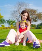 Photo of young mother with cute little daughter sitting down on green grass field in park, beautiful