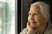 stock photo of sad eyes  - Lovely grandmother looking in a window in a train - JPG