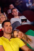 Romantic young couple sitting in cinema, watching movie, smiling.