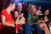 stock photo of cinema auditorium  - Happy girls sitting in multiplex movie theater - JPG
