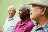 stock photo of sitting a bench  - retired elderly people and free time group of happy senior african american and caucasian male friends talking and sitting on bench in park - JPG