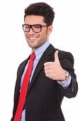 close-up of a young business man showing thumbs up gesture and smiling to the camera, on white