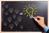 business man drawing many small light bulbs equal a big one. many ideas make a big one