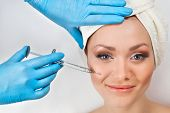 stock photo of lip augmentation  - Young woman receiving a botox injection in her cheek - JPG