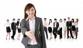 Smiling business executive woman of Asian make a handshake with you in front of her team isolated on