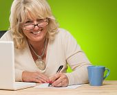 Happy Mature Woman Writing On Paper against a green background