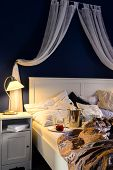 Empty unmade luxury bed romantic feeling with champagne