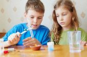 Boy and girl make chemical experiment