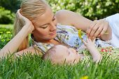 picture of recliner  - Smiling young mother reclines on green grass next to her baby daughter - JPG