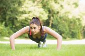 Serious fit woman doing plank position outside on the grass