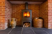 image of chimney  - Roaring fire inside wood burning stove in brick fireplace with basket of cut wood ready for burning - JPG