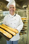 Mature baker presenting proudly some baguettes on a baking tray smiling at camera