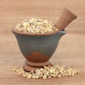Frankincense in a mortar with pestle over papyrus background.