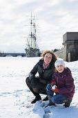 Mother and daughter playing a snowball fight against a sailboat