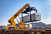 stock photo of railroad car  - Crane lifting up container in railroad yard - JPG