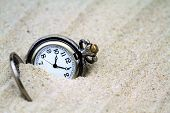 Antique pocket watch buried in sand.