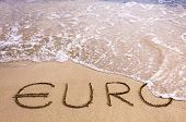 Euro Word Written In The Sand On A Beach, Washed Away By Sea Water