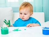 cute baby girl draw finger paints at home in bright living room