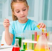 stock photo of flask  - cute little girl with flasks for chemistry - JPG