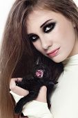 pic of catsuit  - Portrait of young beautiful girl in latex catsuit with smokey eyes makeup and black kitten in her hands - JPG