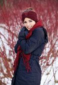 picture of shivering  - Shivering woman with red scarf in a cold winter park - JPG