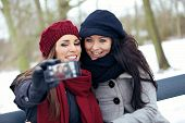 image of two women taking cell phone  - Two beautiful women enjoying the freezing park and taking pictures - JPG