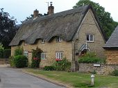 foto of stone house  - A large thactched stone house in a middle England village lane - JPG