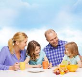 food, family, children, hapiness and people concept - happy family with two kids having breakfast at
