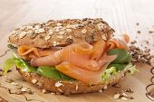 stock photo of bagel  - Whole grain bagel with smoked salmon on wooden background - JPG