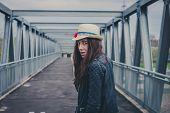 picture of girl walking away  - Pretty girl with long hair walking away on a bridge - JPG