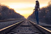Young Adult Girl Balance On Railroad In Sunset Beams