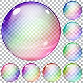 stock photo of orbs  - Set of multicolored transparent glass spheres on a plaid background - JPG