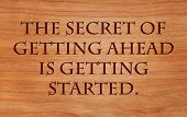 The secret of getting ahead is getting started - motivational quote by Mark Twain on wooden red oak background