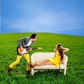pic of mans-best-friend  - Man playing a solo on the guitar with girl lying on the couch and singing together on the green field
