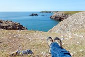 Man's Legs Relaxing On The Rocky Coast Of Southern Wales