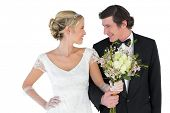 Happy newlywed couple with bouquet looking at each other on white background