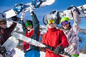 stock photo of snowboarding  - Four happy friends standing together and holding snowboards and skies looking straight