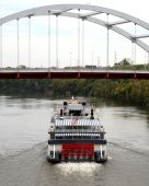Paddleboat Sailing Under A Suspension Bridge