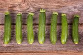 A row of fresh courgettes on an old wood table.