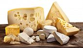 Different types of cheese over old wooden table.File contains clipping paths.