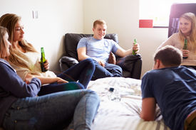 stock photo of underage  - Group Of Teenagers Drinking Alcohol In Bedroom - JPG
