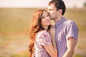 stock photo of windy weather  - Young beautiful sensual couple kissing outdoors in windy weather in the summer on a lavender field - JPG