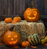 stock photo of gourds  - Two halloween pumpkins with a bale of hay and other gourds - JPG