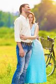 Young Affectionate Caucasian Couple Resting Together In The Park Area With Bicycle