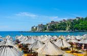 stock photo of yugoslavia  - The straw umbrellas on the beach with the Kalaja citadel on the background Ulcinj Montenegro - JPG