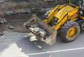 Bulldozer carries  in the bucket ruined asphalt.